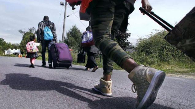 لاجئون قادمون من الولايات المتّحدة يتّجهون نحو ممرّ روكسهام الحدودي في كيبيك/Charles Krupa/AP
