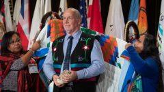 جون هورغان رئيس حكومة بريتيش كولومبيا يتلقّى رداء تكريميّا خلال انعقاد الجمعيّة الاستثنائيّة للأمم الأوائل/ Adrian Wyld/CP