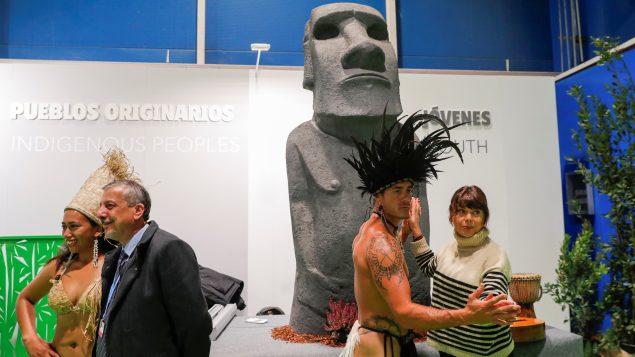 زوّار في المساحة المخصّصة للسكّان الأصليّين في قمّة المناخ في مدريد في 04-12-2019/REUTERS/Susana Vera