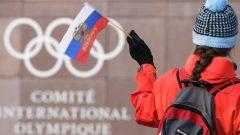 سيّدة تلوّح بعلم روسيا أمام مقرّ اللجنة الدوليّة الأولمبيّة في لوزان في سويسرا/ Fabrice Coffrini/Getty Images