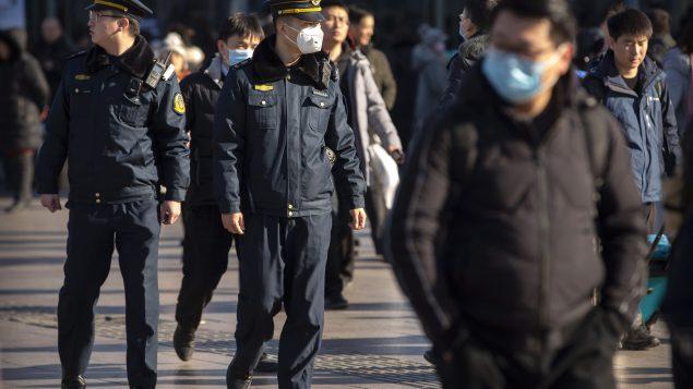 أحد أعوان الأمن في مدينة بيجين يضع قناعا حاميا من فيروس كورونا - 20.01.2020 - AP Photo/Mark Schiefelbein