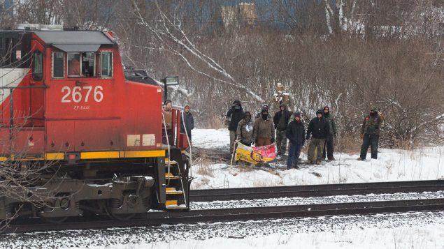 محتجّون موهوك من السكّان الأصليّين في بيلفيل في أونتاريو أثناء مرور قطار تابع لشركة كنديان ناسيونال في 26-02-2020/Lars Hagberg/CP
