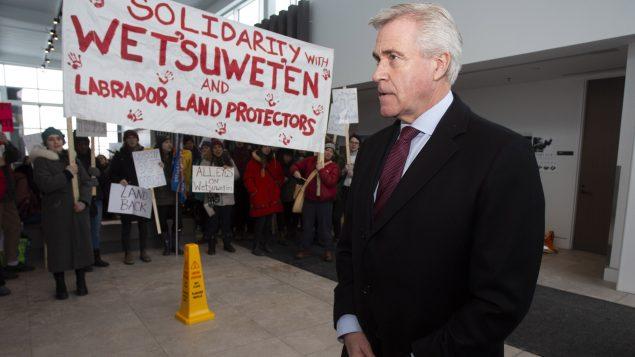 دوايت بول رئيس حكومة نيوفاوندلاند ولابرادور في جامعة ميموريال في سانت جونز وبجانبه لافتة تأييد لأمّة وتسووتين من السكّان الأصليّين التي يعارض زعماؤها الوراثيّون مشروع أنبوب الغاز السائل في بريتيش كولومبيا//Paul Daly/CP