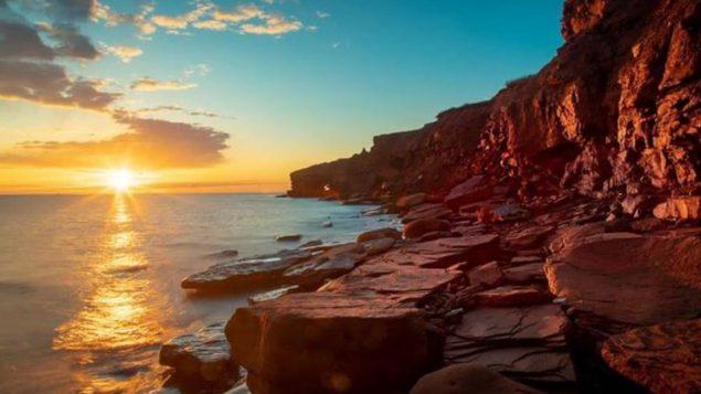 جرف صخري أحمر تحت أشعّة الشمس على ساحل جزيرة برنس إدوارد/André Audet
