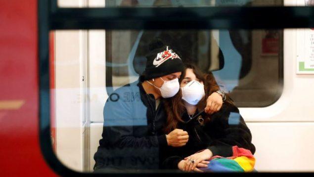 راكبان في قطار الأنفاق في مدينة ميلانو الإيطاليّة وضعا كمّامات للوقاية من فيروس كورونا/Yara Nardi/Reuters