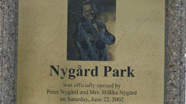 لوحة تكريميّة لمصمّم الأزياء بيتر نيغارد في الحديقة التي تحمل لإسمه في مدينة دولورين في مقاطعة مانيتوبا/Riley Laychuk/CBC/هيئة الإذاعة الكنديّة