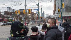 بعض المارّة في أحد شوارع تورونتو وضعوا كمّامات للوقاية من فيروس كورونا/Frank Gunn/CP