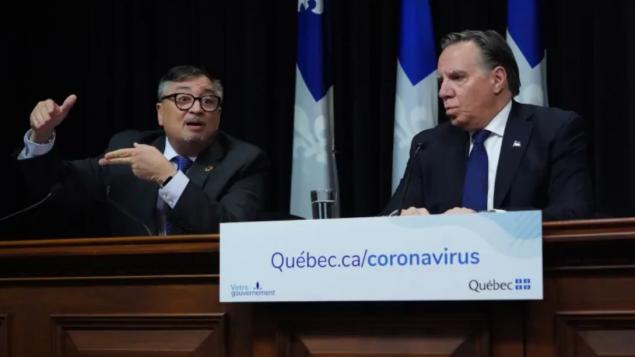 رئيس حكومة كيبيك فرانسوا لوغو (إلى اليمين) ومدير وكالة الصحّة العامّة في المقاطعة أوراسيو أرودا/Jacques Boissinot/CP