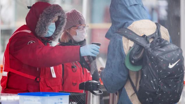 عناصر من الصليب الأحمر يساعدون مشرّدا في مونتريال/Graham Hughes/CP