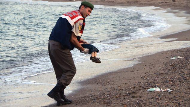 شرطي تركي يحمل جثّة الطفل إيلان كردي - Associated Press