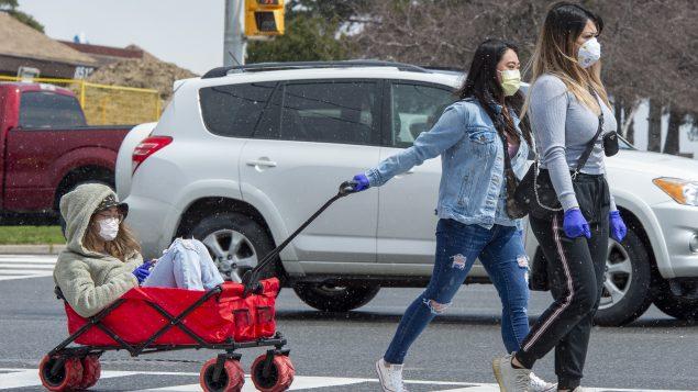 يضع العديد من الأشخاص كمّامات لدى خروجهم للتسوّق للوقاية من وباء كوفيد-19/Frank Gunn/CP