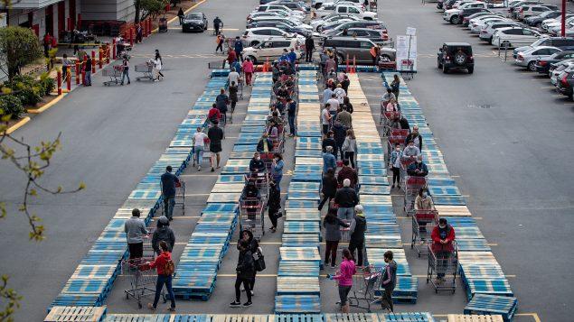 """كبرى شركات البيع بالتجزئة """"كاستكو"""" وضعت ألواحا خشبيّة في مواقف السيّارات التزاما بقاعدة التباعد بين الأشخاص في ظلّ جائحة كوفيد-19/Darryl Dyck/CP"""