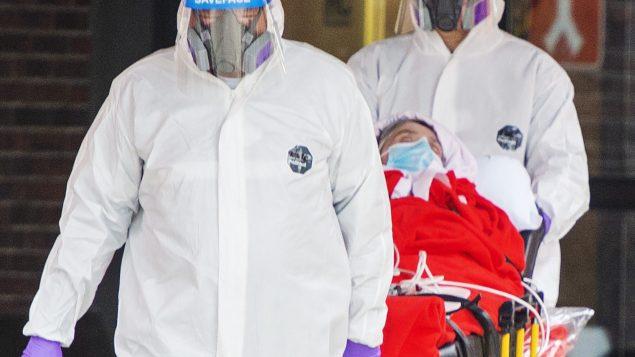 عاملان يرتديان ملابس واقية ينقلان مريضا من مركز لاسال للرعاية الطويلة الأمد في مونتريال//Ryan Remiorz/CP