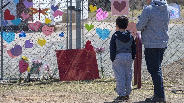 طفل ووالده أمام مكان لتكريم ضحايا حادثة إطلاق النار في نوفا سكوشا/Andrew Vaughan/CP