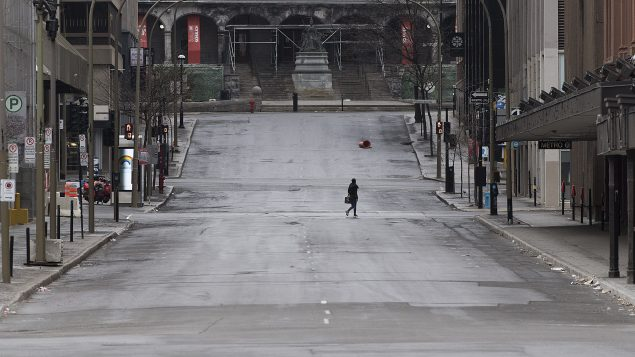 A woman crosses a street in downtown Montreal, Sunday, April 5, 2020, as Coronavirus COVID-19 cases rise in Canada and around the world.THE CANADIAN PRESS/Graham Hughes