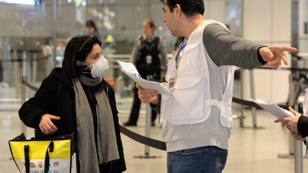 عامل صحّة يعطي إرشادات للمسافرين في مطار مونتريال الدولي في 16-03-2020/Ryan Remiorz/CP