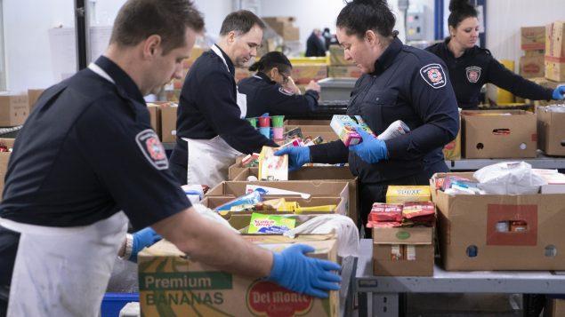 """عناصر من جهاز الإطفاء تطوّعوا لمساعدة بنك الغذاء """"موسون موتريال"""" في 27-03-2020/Paul Chiasson/CP"""