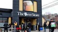 أشخاص ينتظرون أمام متجر للجعة (البيرة) في تورنتو لشراء الجعة وإعادة زجاجات فارغة مع التزامهم بقاعدة التباعد الجسدي في 20-04-2020/Colin Perkel/CP