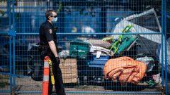 شرطيّ يرتدي كمّامة أمام حديقة عامّة في فانكوفر أمرت السلطات المشرّدين بإخلائها في 09-05-2020//Darryl Dyck/CP