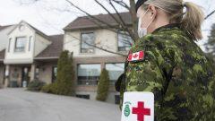 إحدى أفراد القوات المسلحة الكندية أمام مركز لرعاية المسنين في كيبيك يوم 19 أبريل نيسان 2020 - The Canadian Press / Graham Hughes