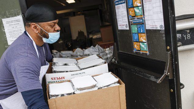 عامل ينقل المساعدات الغذائيّة من مطبخ جماعي في نيوبرنزويك لتوزيعها على المحتاجين/AP Photo/John Minchillo)