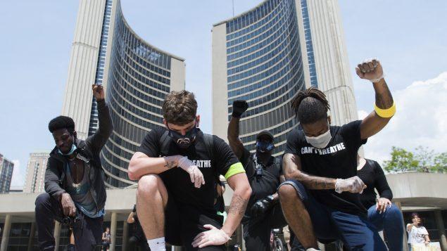 متظاهرين ركعوا ورفعوا قبضتهم خلال المظاهرة المندّدة بالعنصريّة في تورونتو في 05-06-2020/Nathan Denette/CP