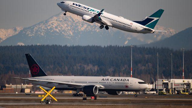 طائرة تابعة لشركة ويست جيت في الأجواء وأخرى تابعة للخطوط الجويّة الكنديّة على المدرج في مطار فانكوفر في 20-03-2020/Darryl Dyck/CP