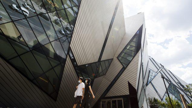 أشخاص وضعوا كمّامات يسيرون أمام متحف تورونتو الملكي في 26-06-2020//Cole Burston/CP