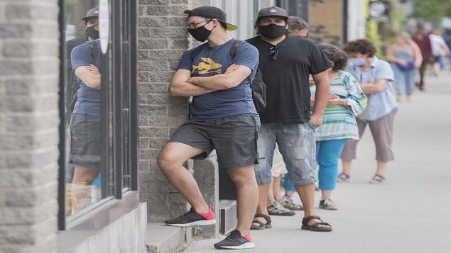 طابور لزبائن يرتدون كمامات أمام متجر في مونتريال - 27 يونيو حزيران 2020 - Graham Hughes / The Canadian Press