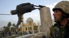 جندي أمريكي يشاهد سقوط تمثال للرئيس العراقي صدام حسين في وسط بغداد ، العراق ، 9 أبريل نيسان 2003 - REUTERS / Goran Tomasevic