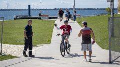 درّاج يلوّح بيده لرجل شرطة في كينغستون في مقاطعة أونتاريو التي شدّدت حكومتها إجراءات الوقاية بعد ارتفاع حالات كوفيد-19/Lars Hagberg/CP