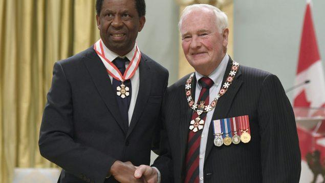 الكاتب الكندي الهايتي داني لافريير (إلى اليسار) يتلقّى وسام الاستحقاق الكندي من حاكم كندا العام ديفيد جونستون في 25-08-2017/Justin Tang/CP