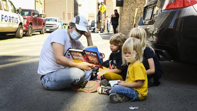 عائلة في أونتاريو تطالع كتابا أمام مركز الكشف عن فيروس كورونا المستجدّ أمام مستشفى سانت مايكل في أونتاريو في في 28-09-2020/Nathan Denette/CP