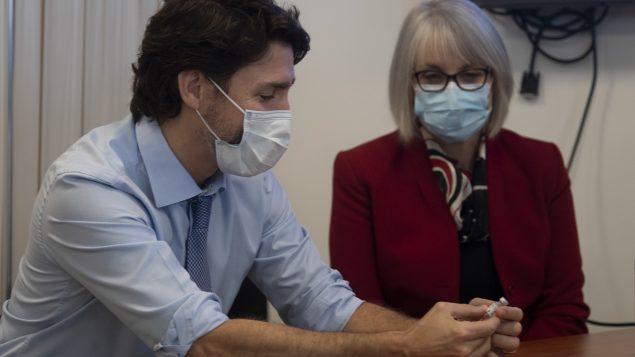 وزيرة الصحّة باتي هايدو تنظر إلى رئيس الحكومة جوستان ترودو الذي يحمل زجاجة فارغة من لقاح فايزر-بيونتيك في مستشفى أوتاوا في 15-12-2020/Adrian Wyld/CP