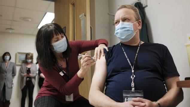 شخص يتلقّى لقاح فايزر- بيونتيك المضادّ لفيروس كورونا المستجدّ في المستشفى العام في مدينة ريجاينا في 15-12-2020/
