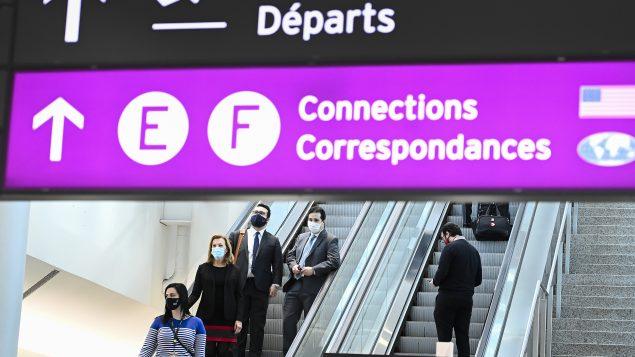 كريستين إليوت وزيرة الصحّة في أونتاريو (إلى اليسار) تضع كمامة أثناء مغادرة مطار بيرسون الدولي في تورونتو حيث تفقّدت محطّات الكشف عن فيروس كورونا المستجدّ في صالات الوصول في 07-01-2021//Nathan Denette/CP