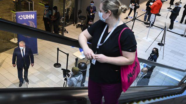 رئيس حكومة أونتاريو دوغ فورد يتحدّث إلى الصحفيّين تحت أنظار عاملة صحّة في عيادة تطعيم في تورونتو في 07-01-2021/Nathan Denette/CP