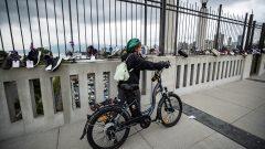 سيّدة تقود درّاجتها فوق جسر بورارد في فانكفر حيث عُلّقت أحذية ضحايا الجرعات المفرطة في يوم التوعية على المخدّرات في 31-08-2021/Darryl Dyck/CP
