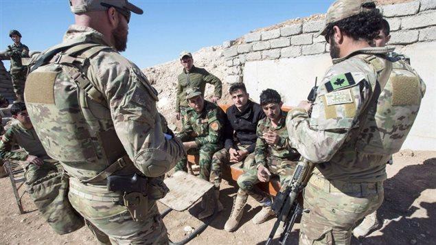 جنود كنديّون من الوحدات الخاصّة يتحدّثون إلى عناصر من قوّات البشمركة التابعة لإقايم كردستان العراق عام 2017 /Ryan Remiorz/CP