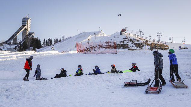 أطفال يتزحلقون على الثلج في حديقة عامّة في مدينة كالغاري في 16-03-2021/Jeff McIntosh/CP