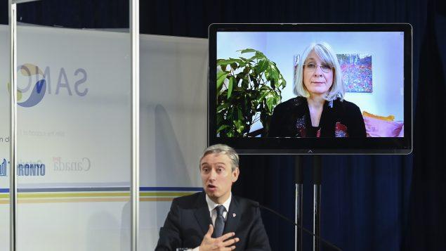 فرانسوا فيليب شامبان وزير الابتكار والعلوم والصناعة، وبدت في خلفيّة الصورة وزيرة الصحّة باتي هايدو، خلال الإعلان عن مشوع إنشار مصنع لقاحات الإنفلونزا في تورونتو في 31-03-2021/Nathan Denette/CP