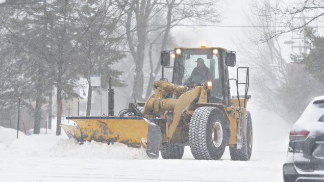 تعمل الجرّافات على رفع الثلوج من الطرقات والأرصفة لتسهيل تنقّل السيّارات والمارّة بعد العواصف الثلجيّة/Jacques Boissinot/ CP