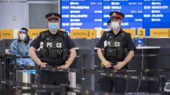 عناصر من الشرطة وعمّال الصحّة في قاعة الوصول في مطار تورونتو حيث يخضع المسافرون الواصلون إلى كندا لاختبار كورونا/Frank Gunn/CP