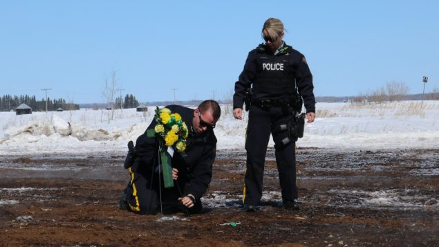 عنصران من الشرطة الملكيّة الكنديّة يضعان باقة من الزهر في موقع الحادثة التي أودت بحياة لاعبي فريق برونكوس للهوكي من سَسكتشوان عام 2018 /CBC/هيئة الإذاعة الكنديّة