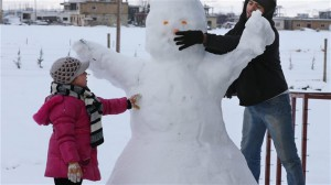 A Syrian man and his daughter make a snowman at the refugee camp in al-Majdal village, Bekaa Valley, East Lebanon on Jan. 8, 2015. A powerful winter storm swept through the region, killing several Syrian refugees in Lebanon and forcing thousands of others who have fled their country's civil war to huddle together for warmth. Photo Credit: AP / Hussein Malla