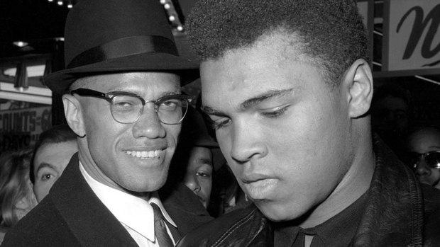 مالكولم إكس إلى اليسار بصحبة الملاكم الأميركي في فئة الوزن الثقيل في مطلع مهنته، محمد علي (الأول من مارس آذار 1964) موقع راديو كندا -