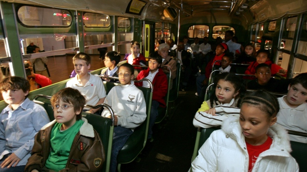 Students sit next to each other on the actual bus where Rosa Parks, a black woman, refused to give up her seat to a white man 50 years ago in Alabama, during their school visit to Henry Ford Museum in Dearborn, Michigan. (Rebecca Cook/Reuters)