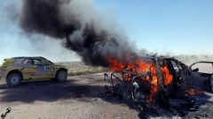 The 2014 race goes on, right past the burning wreckage of Kazakhstani drivers Bauyrzhan Issabayev and Gabdulla Ashimov's car, during the second stage of the Dakar Rally from San Luis to San Rafael, Argentina, on Jan. 6. (Jean-Paul Pelissier/Reuters)