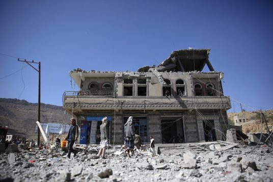 People gather at the site of a house damaged by Saudi-led airstrikes in Sanaa, Yemen, Monday, Jan. 4, 2016. According to U.N. figures, the war in Yemen has killed at least 5,884 people since March, when fighting escalated after the Saudi-led coalition began launching airstrikes targeting the Houthi rebels. (AP Photo/Hani Mohammed)