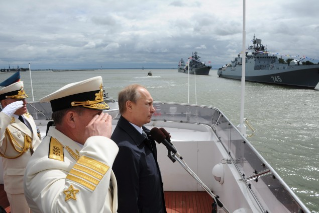 In this Sunday, July 26, 2015 file pool photo, Russian President Vladimir Putin, centre, reviews a Navy parade in Baltisk, western Russia, during celebration for Russian Navy Day. Mikhail Klimentyev/RIA-Novosti